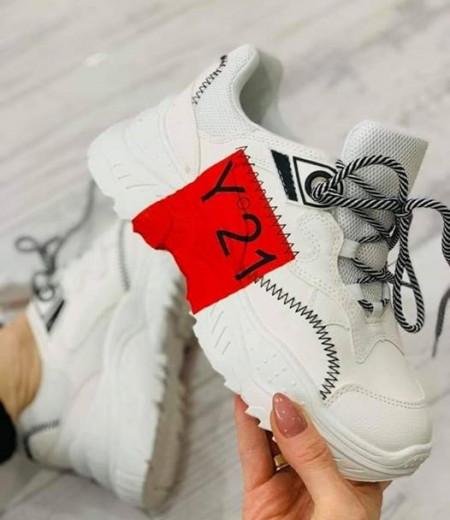Białe sportowe sneakersy z czerwonym akcentem